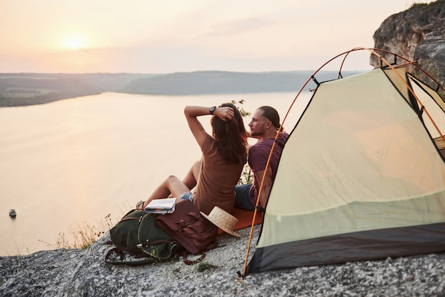 Happy couple sitting in tent with a view of lake during hiking trip. adventure vacations concept