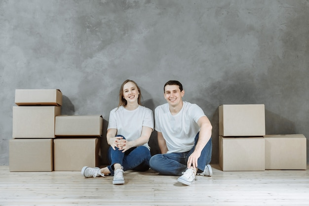 Happy couple sitting together on the floor among cardboard boxes in the apartment.