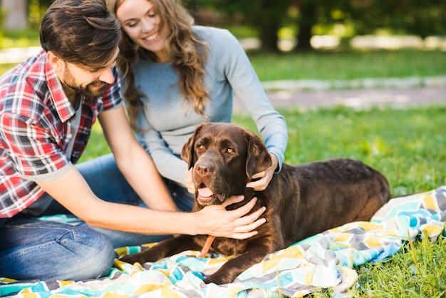 Счастливая пара, сидя со своей собакой в саду