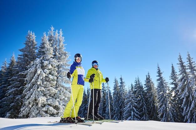 スキーリゾートでスキーをする前にスキーでポーズをとる幸せなカップルのスキーヤー