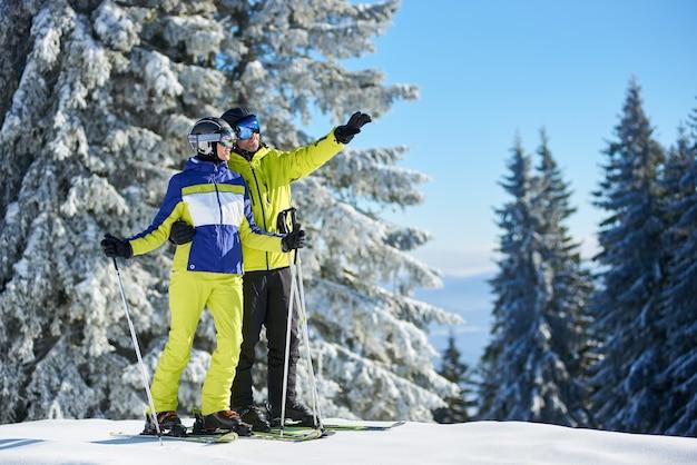 스키장에서 스키를 타기 전에 스키에 포즈를 취하는 행복한 커플 스키어