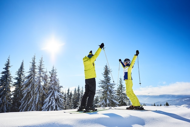 Happy couple skiers standing on mountain edge, rejoicing, raising hands up. clear blue sky over winter mountain nature.