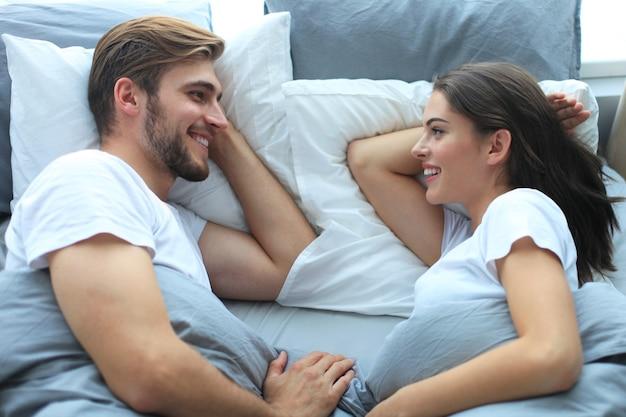 집에서 편안한 침대에서 자는 행복한 커플.