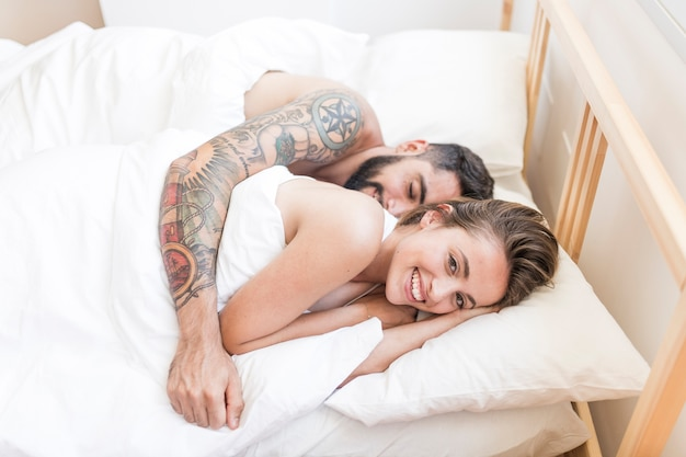 Happy couple sleeping together on bed