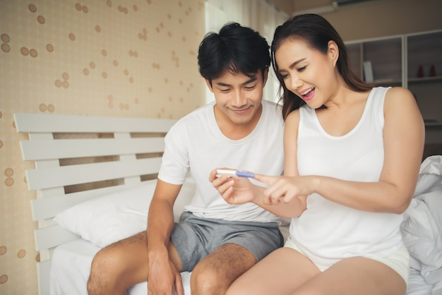 Happy couple smiling after find out positive pregnancy test in bedroom