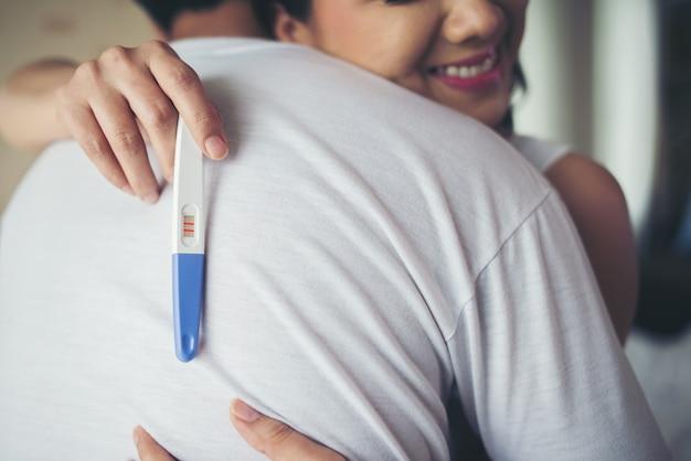 寝室で肯定的な妊娠検査を見つけた後に笑う幸せなカップル