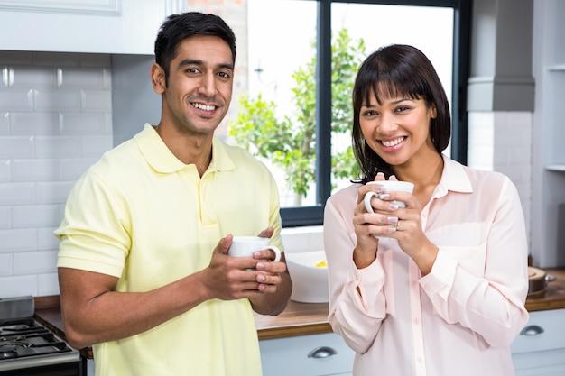 カップを持ってカメラで笑顔の幸せなカップル