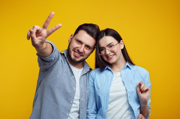 Happy couple smiling and showing peace gesture over yellow wall