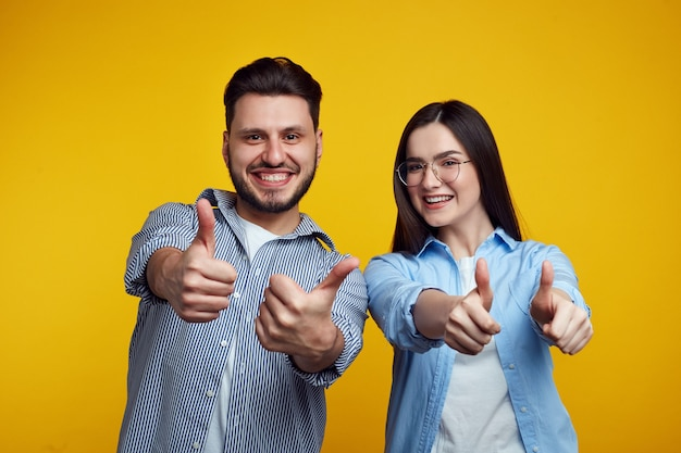 Happy couple smiling and showing thumbs up over yellow wall
