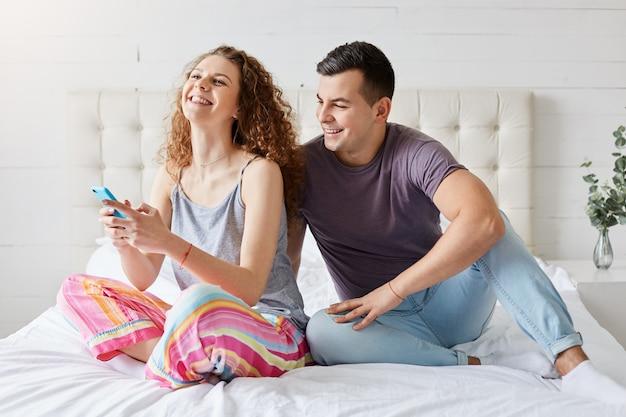 幸せなカップルは寝室で朝の時間を過ごし、スマートフォンでソーシャルネットワークを確認し、常に連絡を取り合い、友達とコミュニケーションをとる、快適なベッドで笑って座っている携帯電話を持つ家族