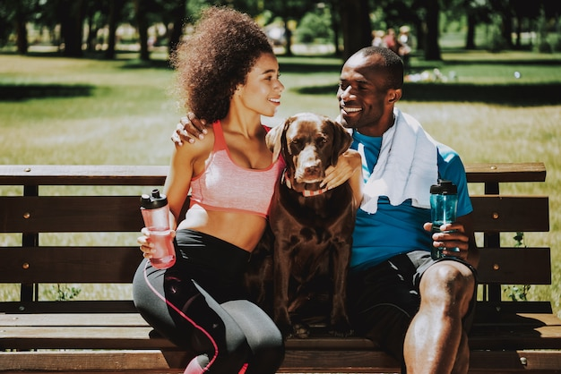 Happy couple in sportswear petting adorable brown dog
