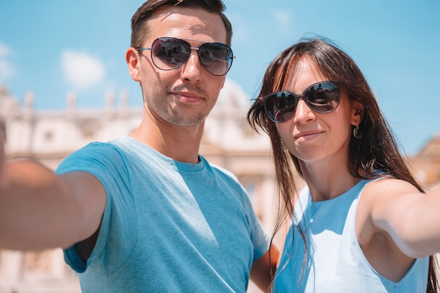 Happy couple at st. peter's basilica church in vatican, rome.