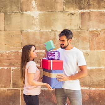 Happy couple stacking gifts against grunge wall