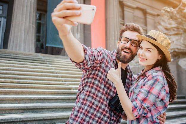Счастливая пара вместе стоять и ставить на камеру. он держит телефон. она показывает большой палец вверх. они стоят рядом с лестницей.