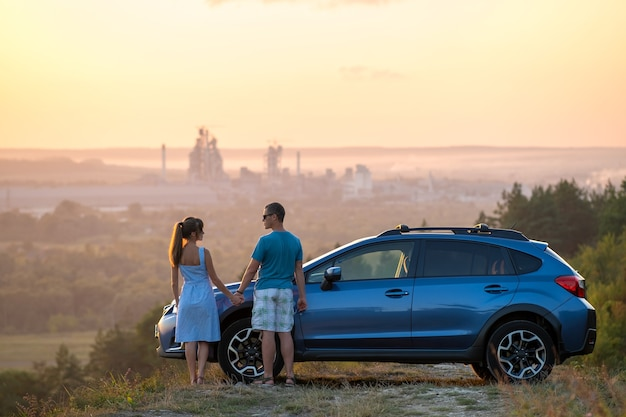 暖かい夏の夜の新婚旅行のロードトリップ中にsuv車の横に立っている幸せなカップル。車で一緒に旅行を楽しんでいる若い男性と女性。