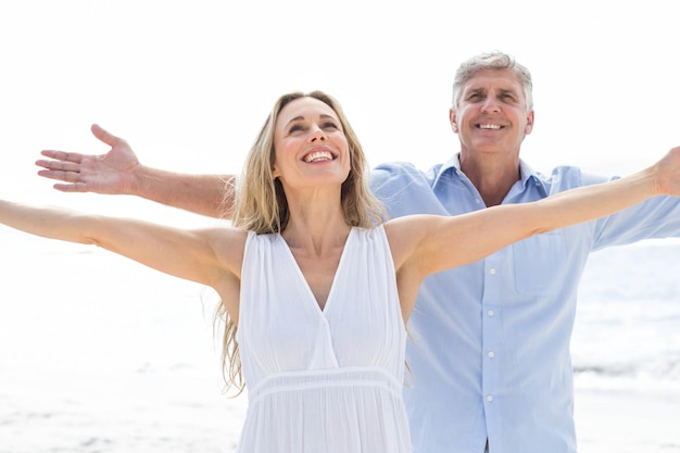 Happy couple standing by the sea arms outstretched
