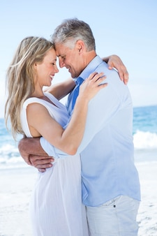 Happy couple standing by the sea and hugging each other