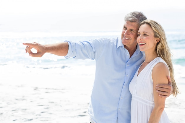 Happy couple standing by the sea and pointing something
