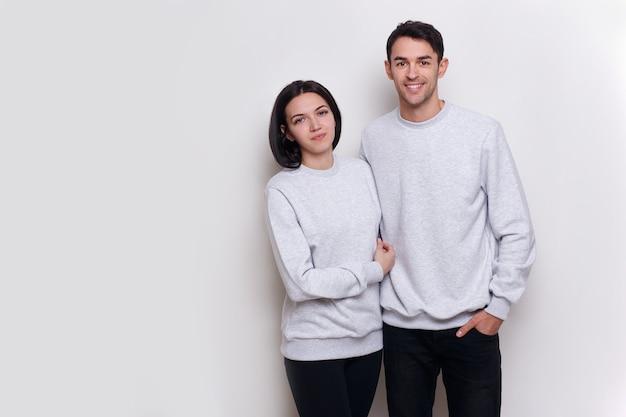 Счастливая пара стоя обнял и улыбается на белом фоне. место для текста.