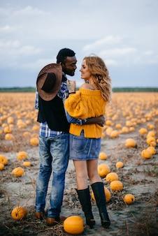 カボチャ畑に立っている幸せなカップル