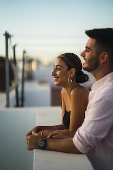 バルコニーに立って、一緒にロマンチックな時間を過ごしている幸せなカップル