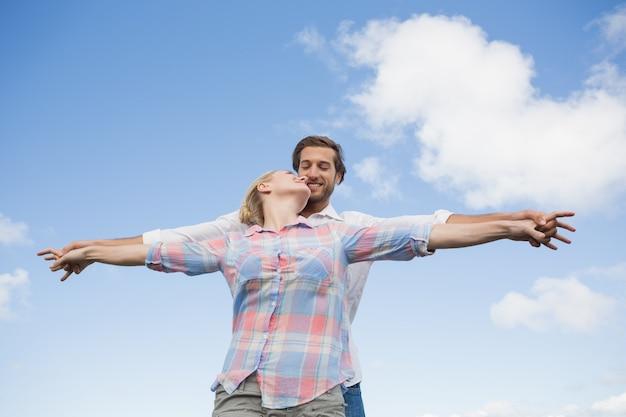 Счастливая пара, стоя на улице с оружием, растягивается поцелуи