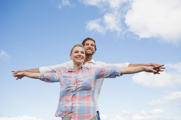 Счастливая пара стоял снаружи с вытянутыми руками