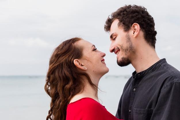 Happy couple standing on sea shore