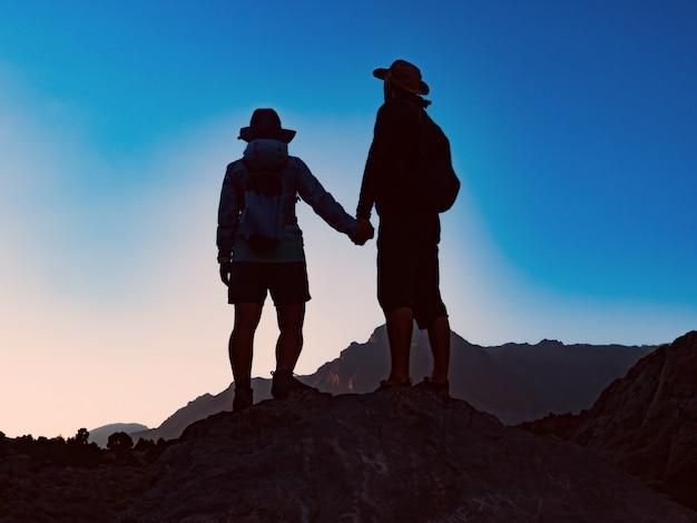 Happy couple standing together on the peak of mountain and watching at breathtaking view at sunset
