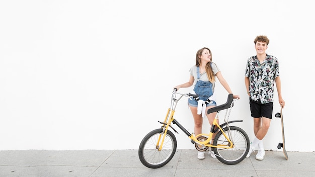 Happy couple standing with bicycle and skateboard on sidewalk