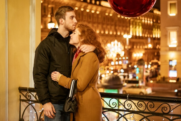 A happy couple stands in an embrace on the street in the evening in the festive lights