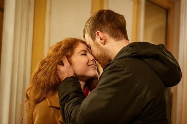 Una coppia felice sta in un abbraccio per strada la sera sotto le luci festive