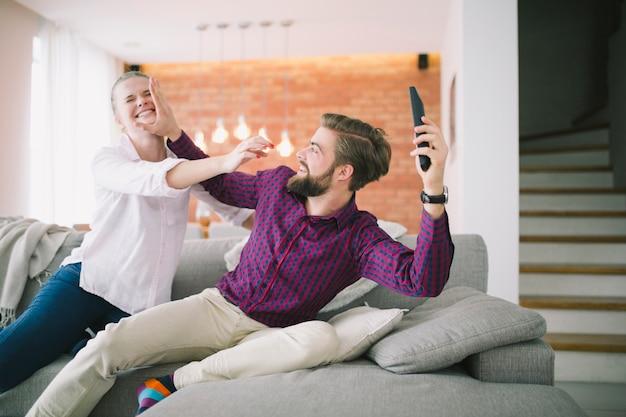 Счастливая пара борется за пульт дистанционного управления