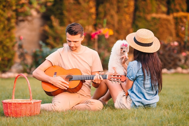 Happy couple on summer picnic. man play the guitar and woman with white puppy