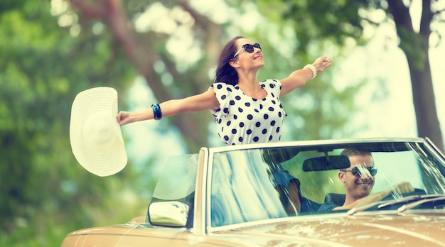 Happy couple on a summer roadtrip with girl sitting on top of a convertible back seat, arms open, hat in her hand.