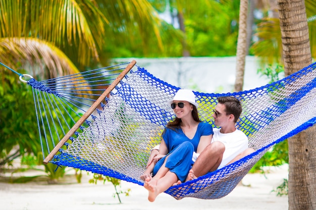 Happy couple on summer vacation relaxing in hammock
