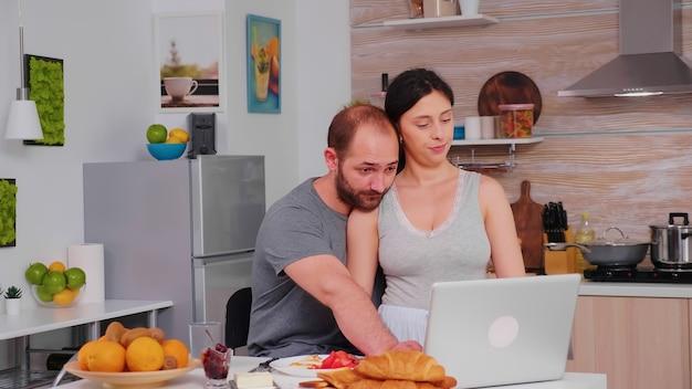 Coppia felice navigando su internet utilizzando il computer portatile durante la colazione in cucina. marito e moglie sposati in pigiama che utilizzano la tecnologia moderna online di internet, sorridenti e felici al mattino. leggendo bene