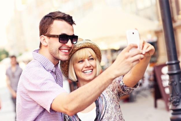 観光しながら自分の写真を撮る幸せなカップル