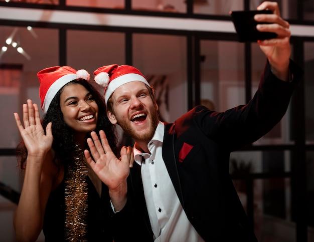 Счастливая пара, делающая селфи на вечеринке в канун нового года