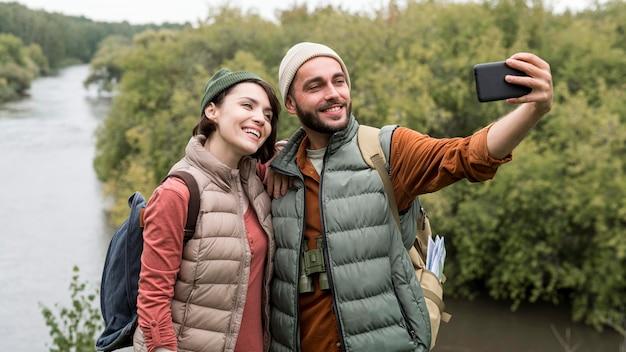 자연 속에서 스마트 폰으로 selfie를 복용하는 행복 한 커플