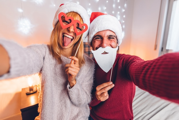 Happy couple taking funny selfie celebrating christmas time at home