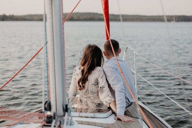 Happy couple taking a romantic cruise on the sail boat.