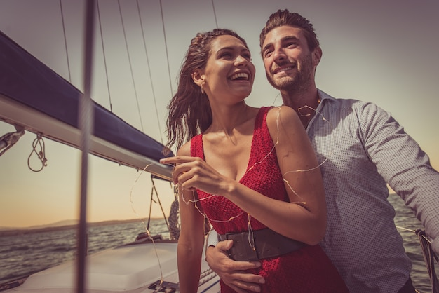 Happy couple taking a romantic cruise on the sail boat
