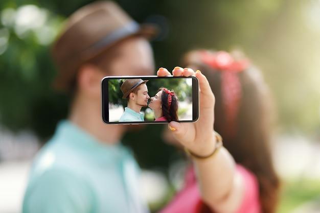 스마트 폰으로 자기 초상화 사진을 찍고 행복 한 커플