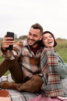 ピクニックでselfieを取る幸せなカップル