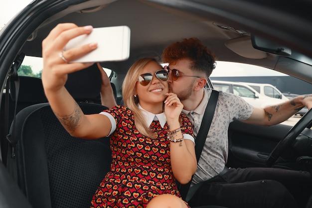Счастливая пара, принимая selfie в машине