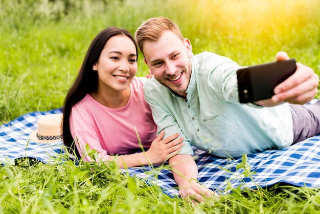Happy couple taking selfie lying