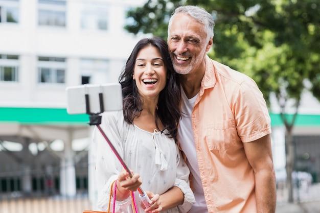 Happy couple taking selfie on monopod