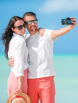 Happy couple taking a selfie photo on white beach. two adults enjoying their vacation on tropical exotic beach Premium Photo