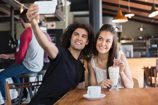 レストランに座っている間幸せなカップル撮影selfie